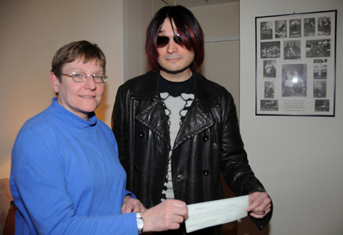 Jane Hoffman of the Mayor's Alliance for NY's Animals accepts a donation from John on behalf of the Osaka Popstar Devil Dog Art show. Over $5,000.00 was raised for the Picasso Veterinary Fund!